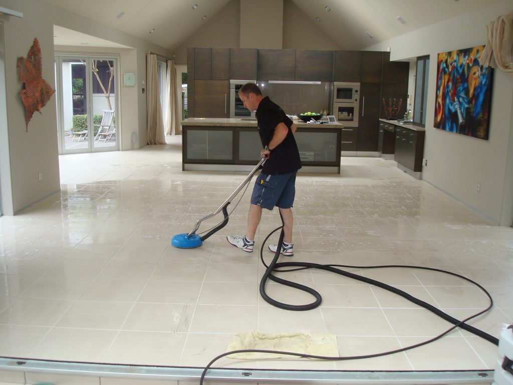 Action shot of a GroutPro franchisee performing a thorough tile and grout clean in the tiled dinning room and kitchen